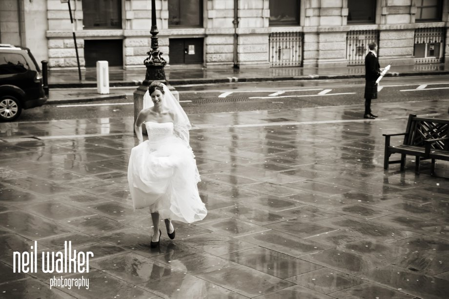 A bride running in the rain in London
