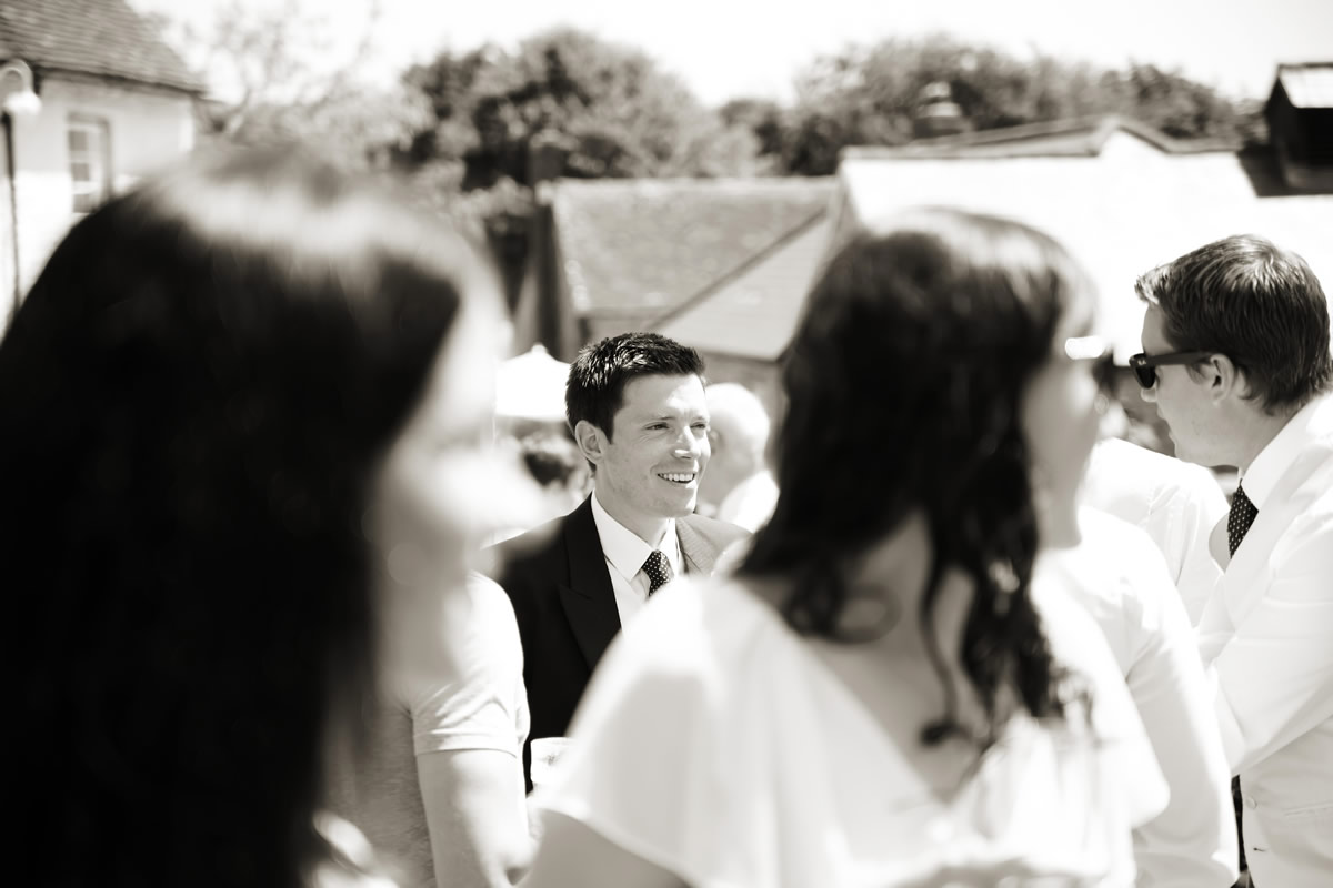 the groom talking to guests at his wedding