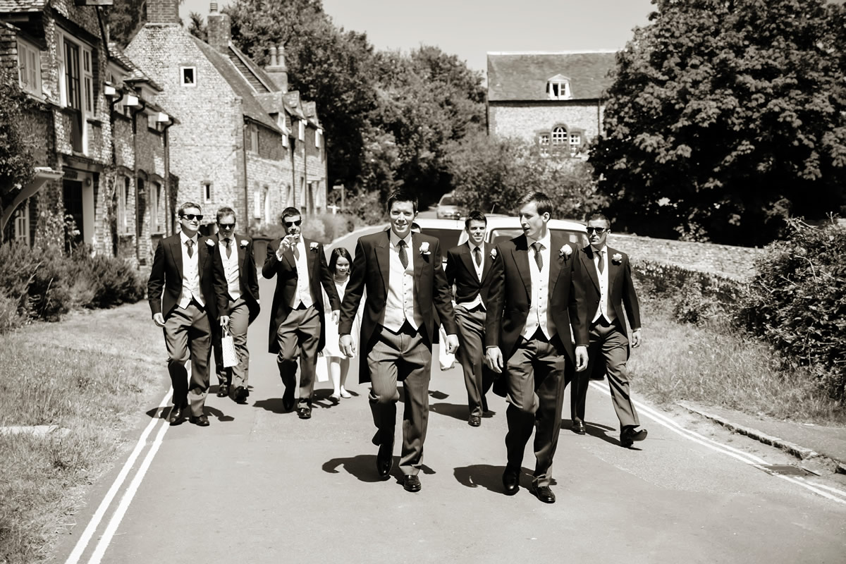 the groomsmen walk to the church
