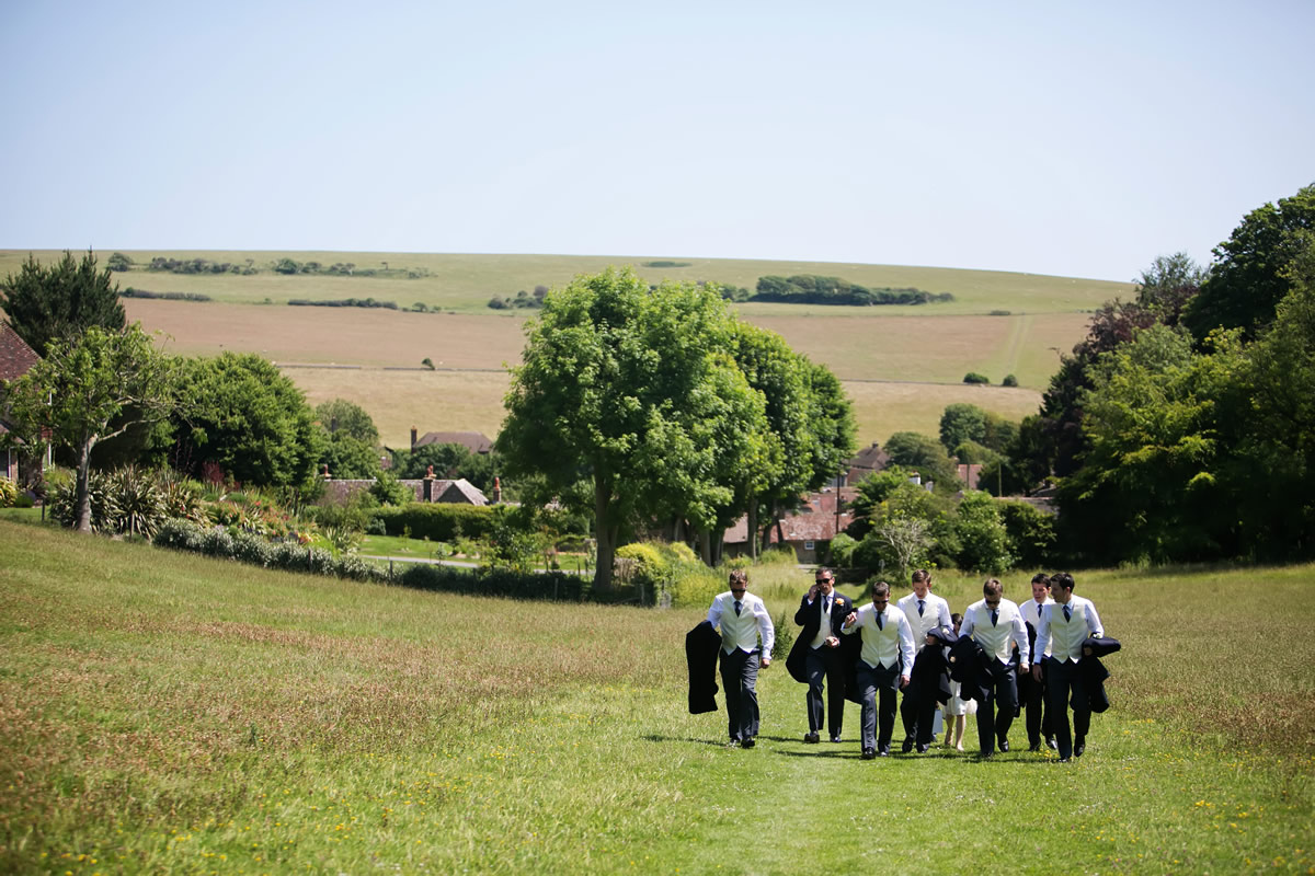 the groom & the ushers walking up the hill to the church