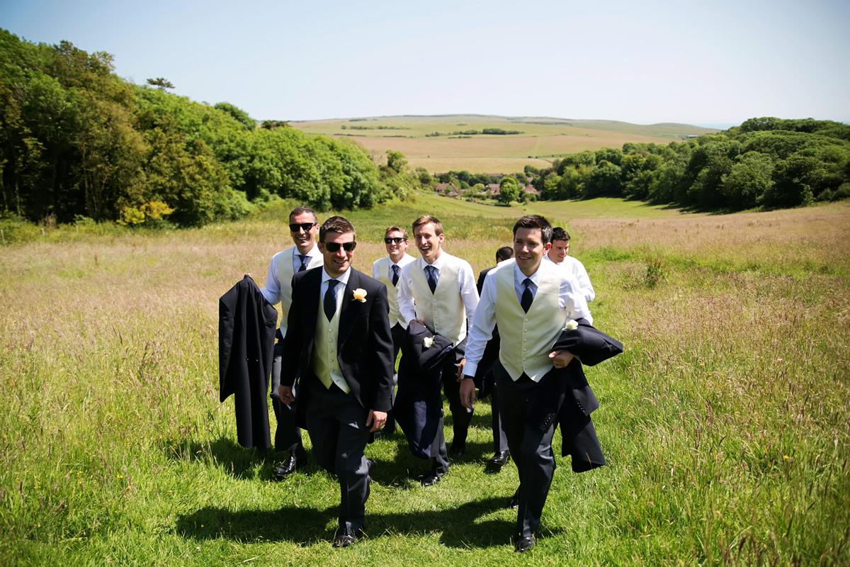 the groom & ushers taking off their coats on a hot day in West Sussex