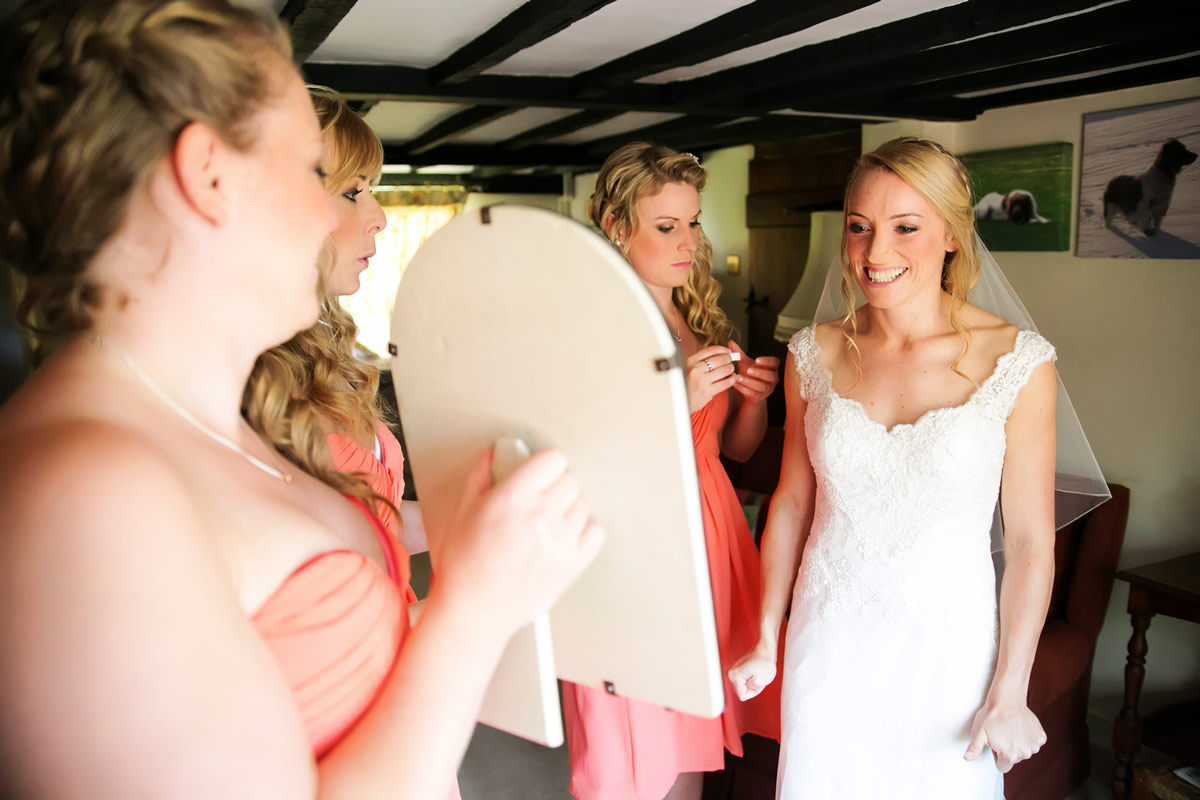 the bride looking at herself in her wedding dress in the mirror