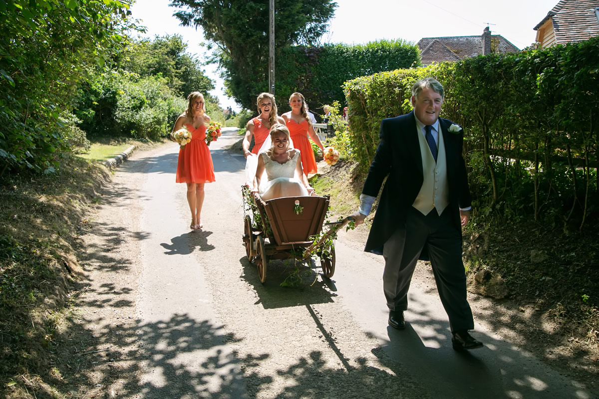 the father of the bride wheeling the bride to her ceremony in a cart