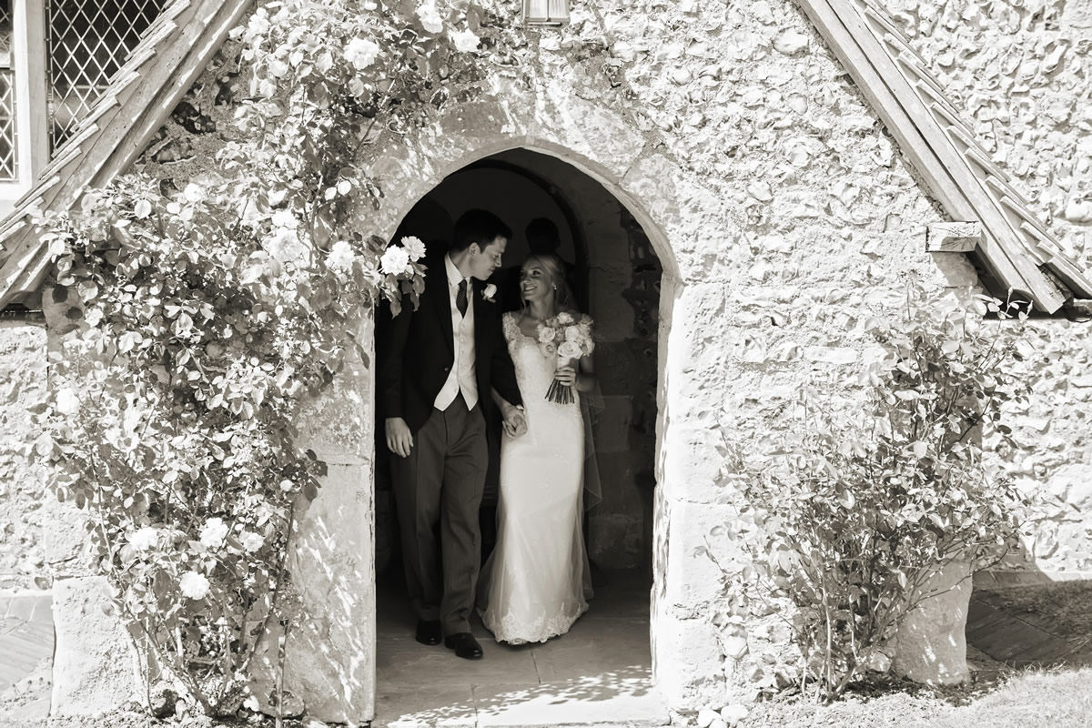 the bride & groom in the doorway to the church