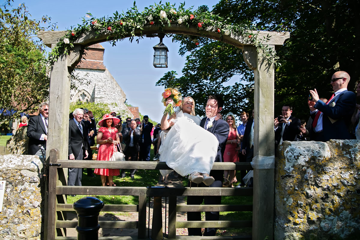 the bride being lifted over the church gate