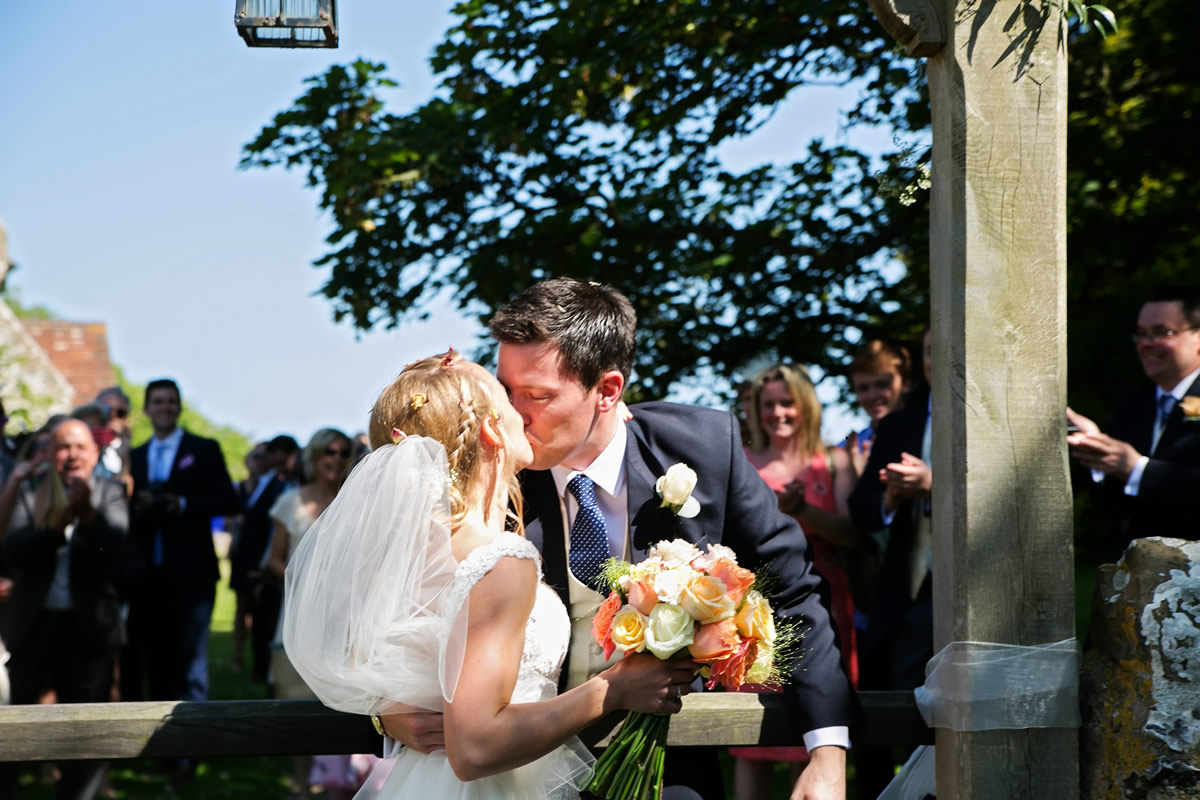 the bride & groom kissing over the church gate