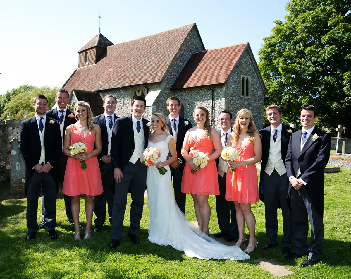 the bridal party in the gardens of the church