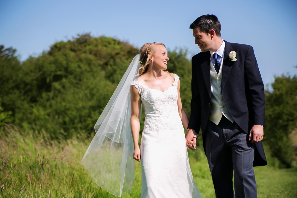the bride & groom walking together at this West Sussex wedding
