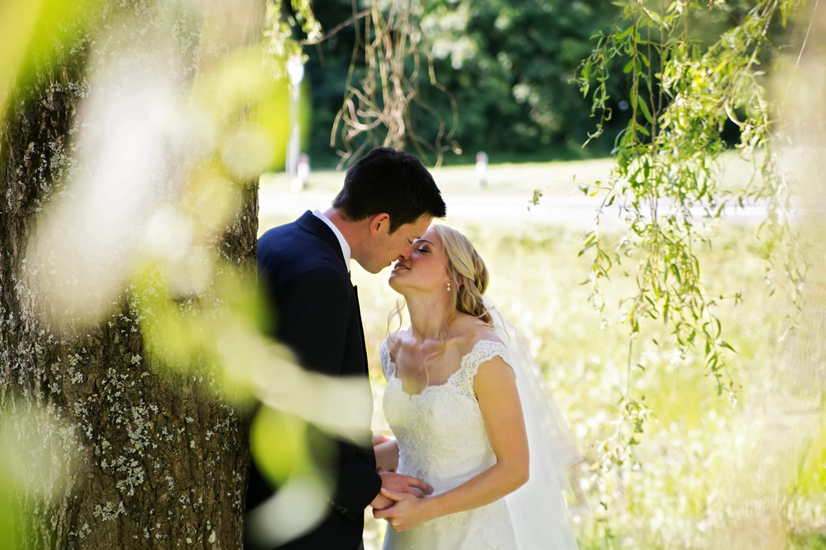 the bride & groom kissing under a tree