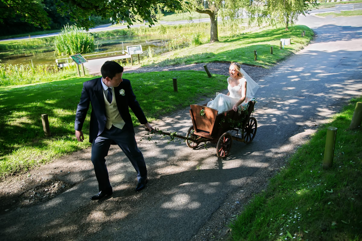 the groom wheeling the bride to the reception in a cart