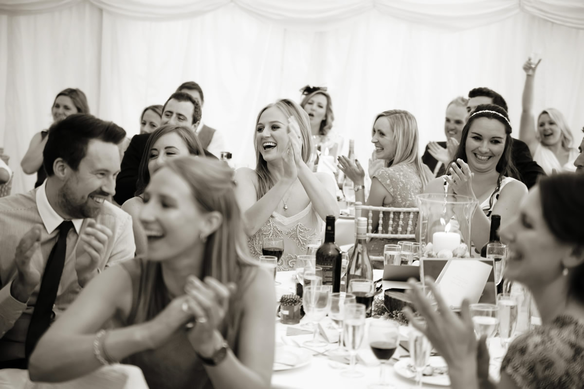 guests laughing at the groom's speech