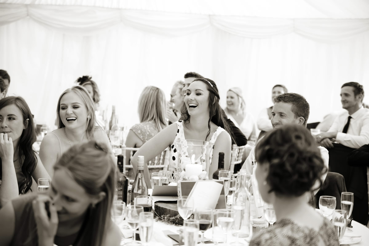 a guest laugh's at the speeches at this West Sussex wedding