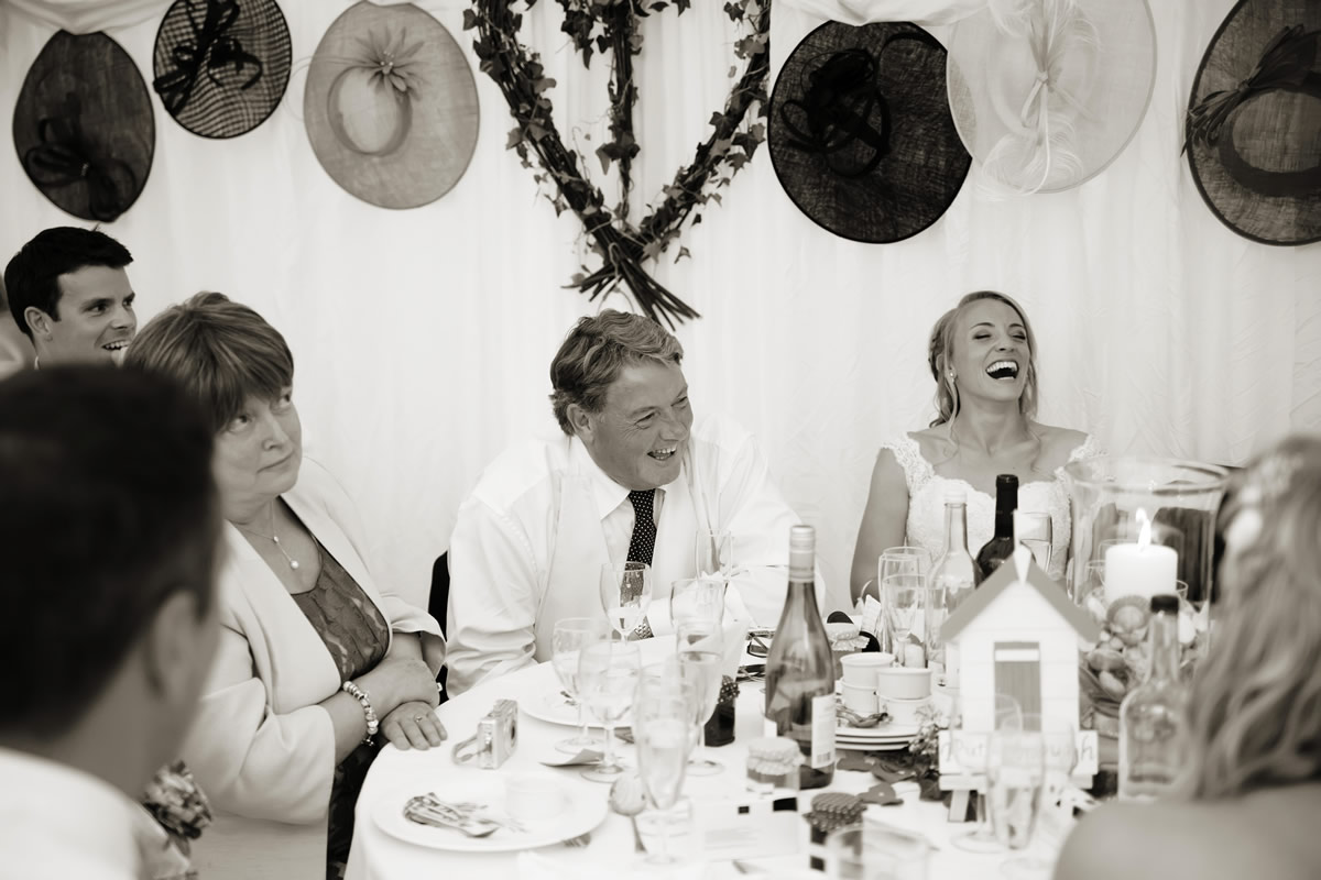 the father of the bride laughing as he listens to the groom's speech