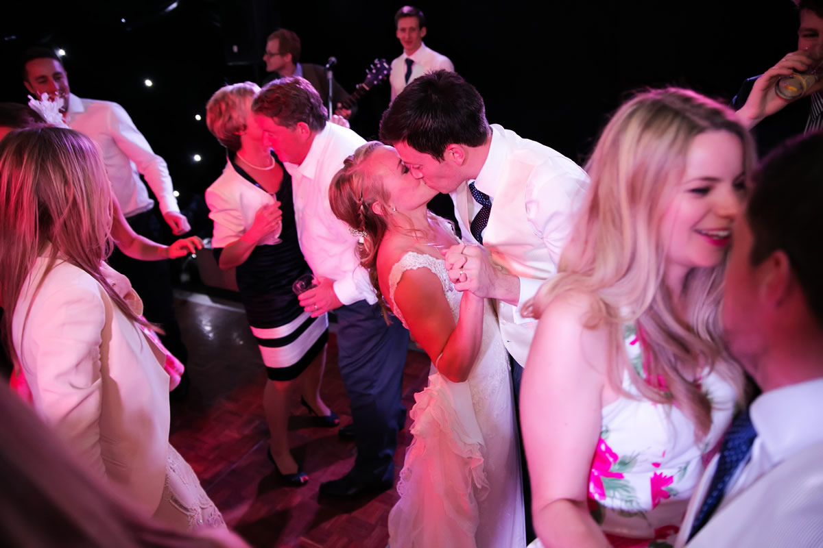 the happy couple kiss on the dance floor with guests dancing around them