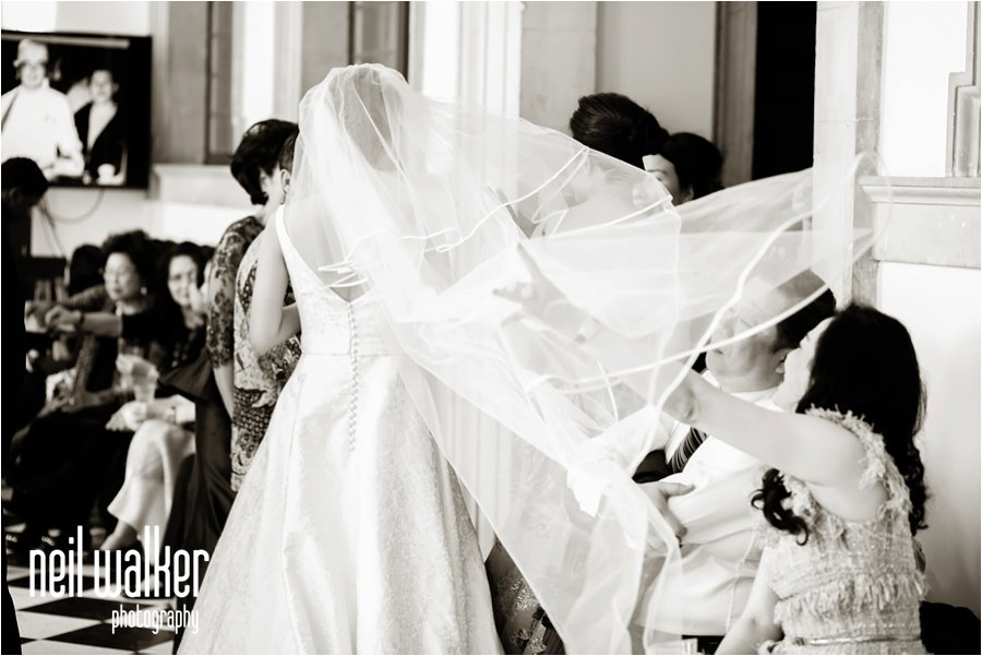 A brides veil catches the wind at her wedding in London
