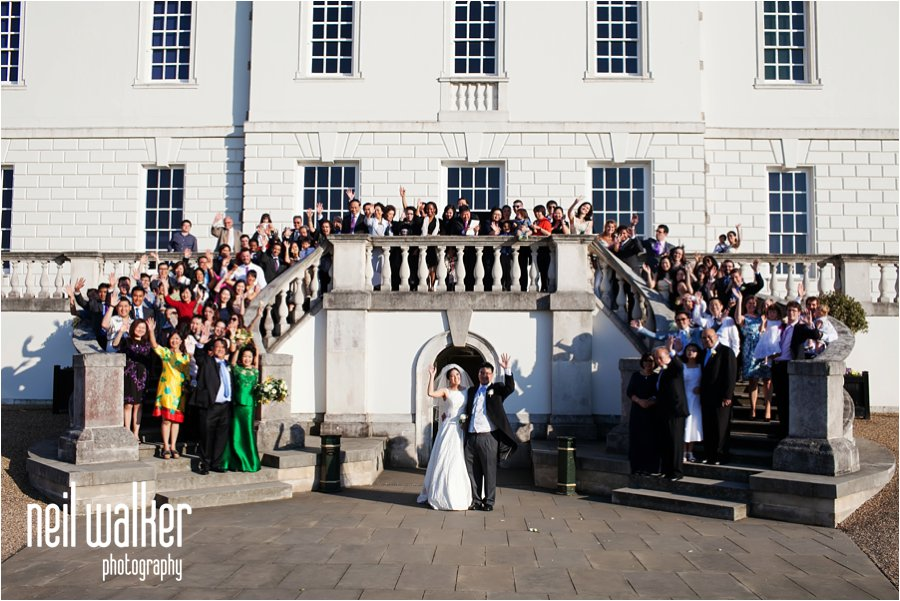 A big group shot of all the guests at a wedding at the front of the Queens House in London