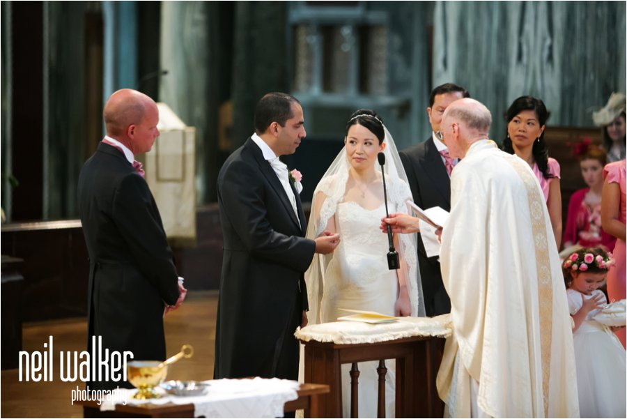 A bride and groom saying their vows in Westminster Cathedral in London