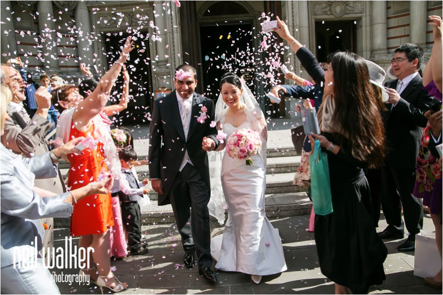 Guests throw confetti over a bride & groom outside Westminster Cathedral in London
