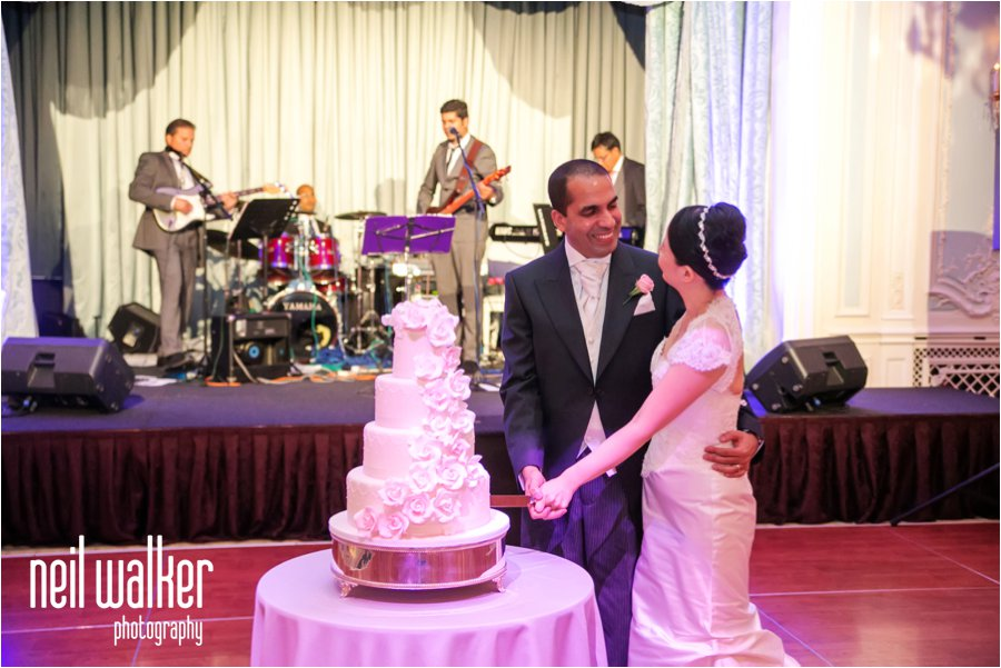 A bride & groom with a wedding cake at the Savoy Hotel in London