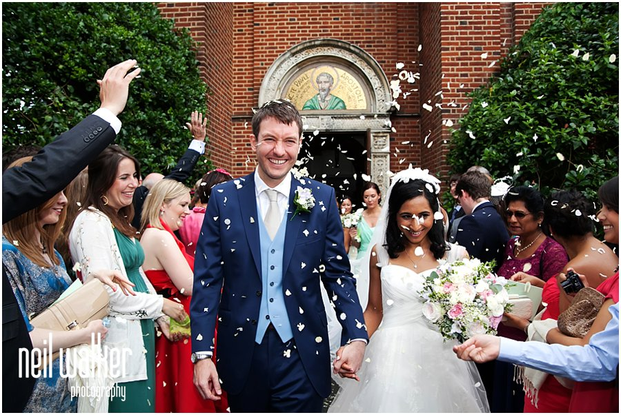 a bride & groom being showered in confetti