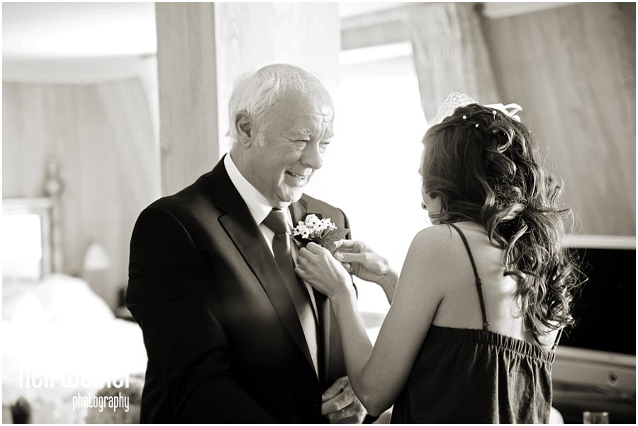 a bride with her father, putting in his buttonhole at a London wedding