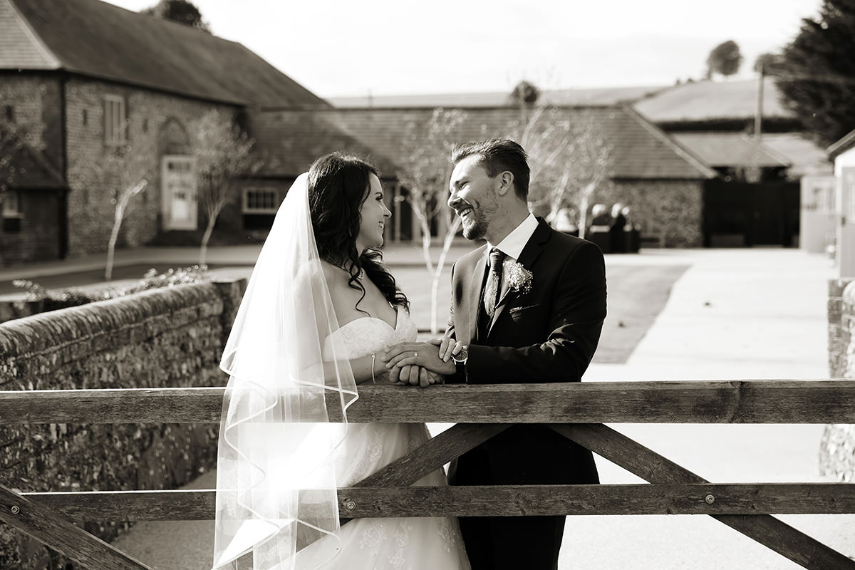 a bride & groom standing by a gate at Farbridge
