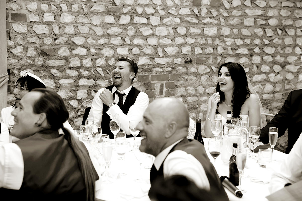 a bride & groom laughing at wedding speeches
