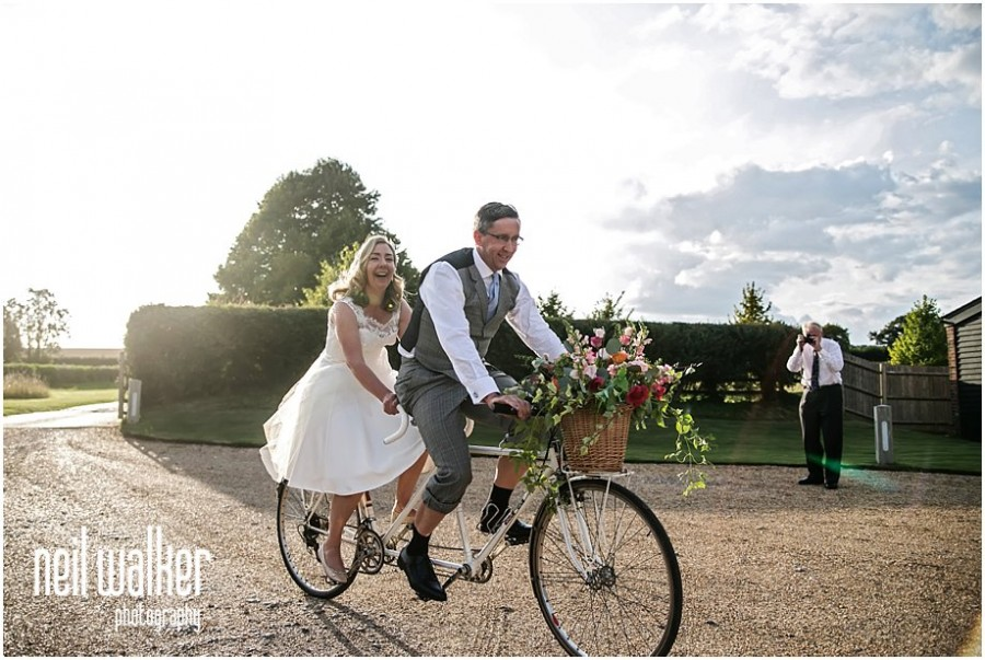 A bride & groom on a tandem at a Sussex wedding
