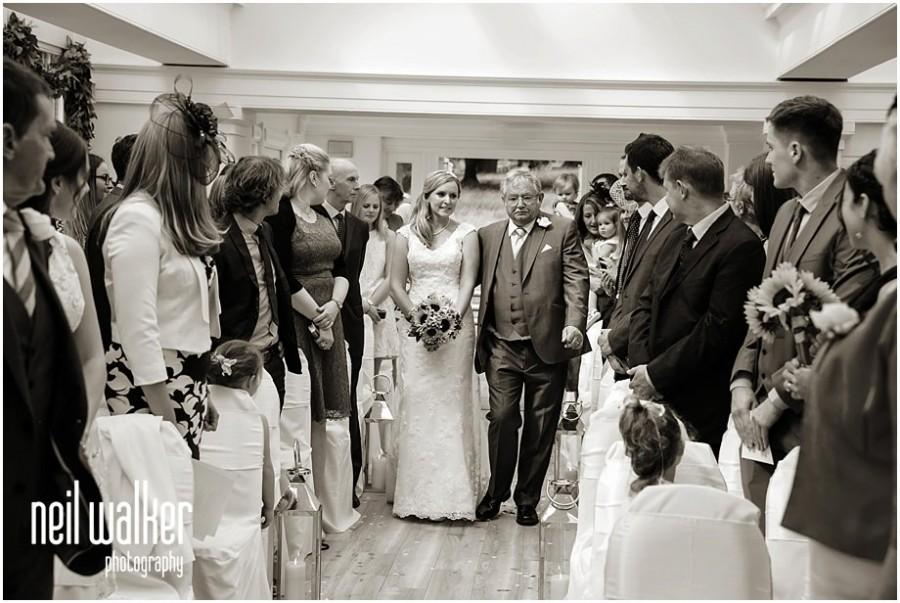 A bride walking down the aisle at Pembroke Lodge