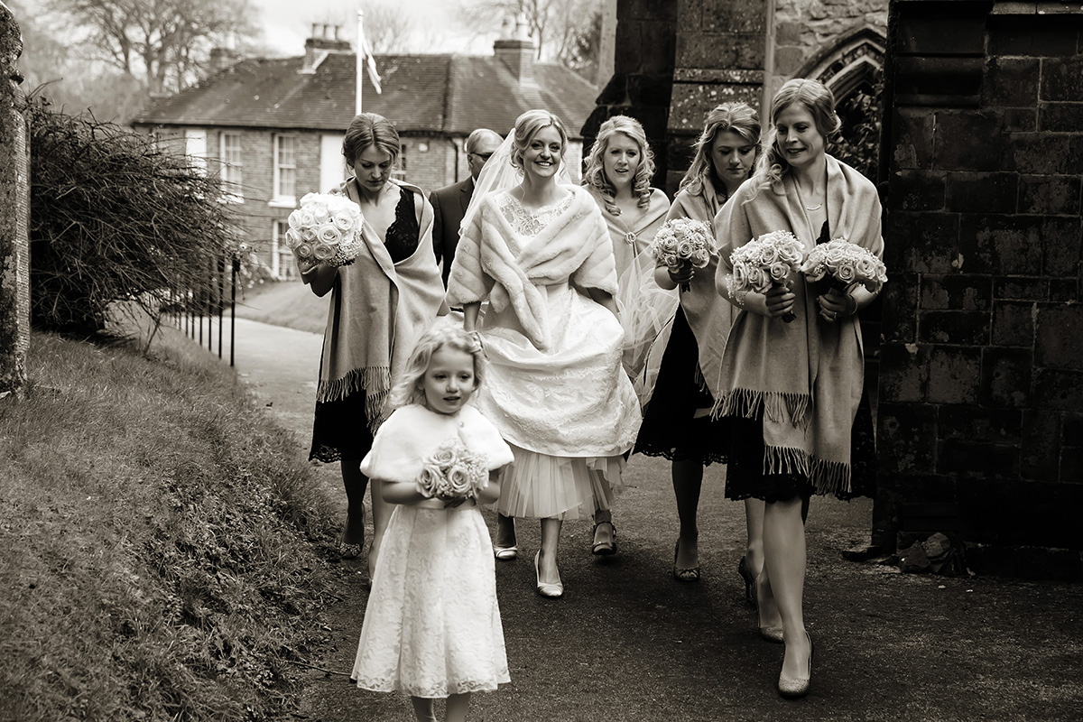bride walking with her bridesmaids to the church laughing
