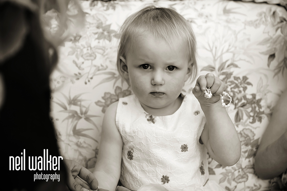 a very young flower girl holding her bracelet
