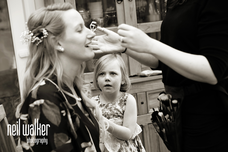 a flower girl looking on while the bride has her makeup done