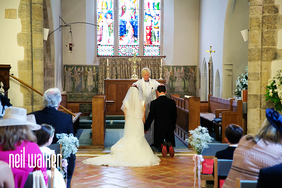 the bride & groom kneel in the church