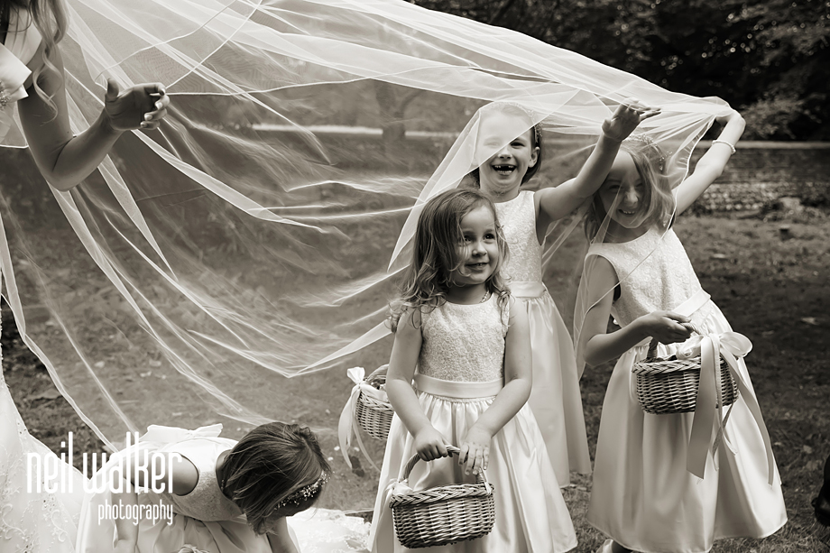 flower girls peeking out from under the bride's veil