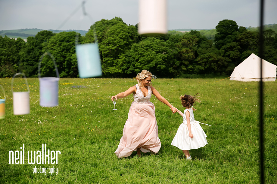 a bridesmaid playing with a flower girl