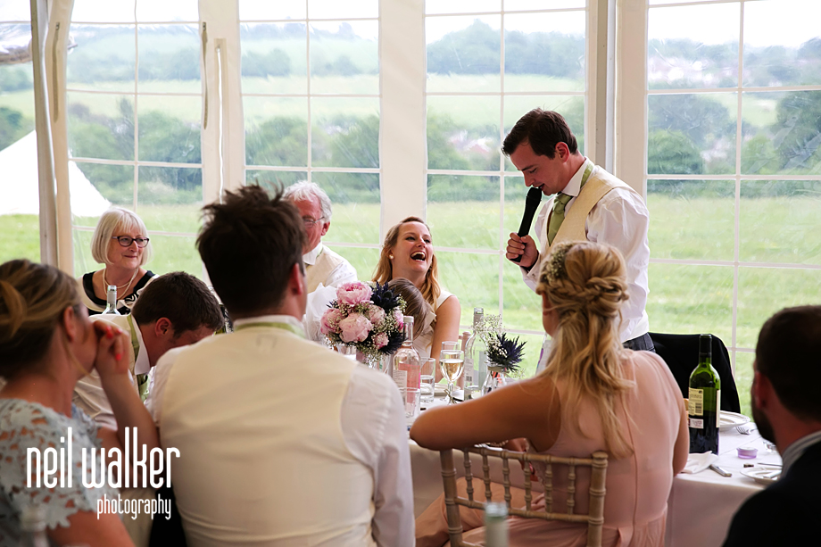 the bride laughing at the groom's speech