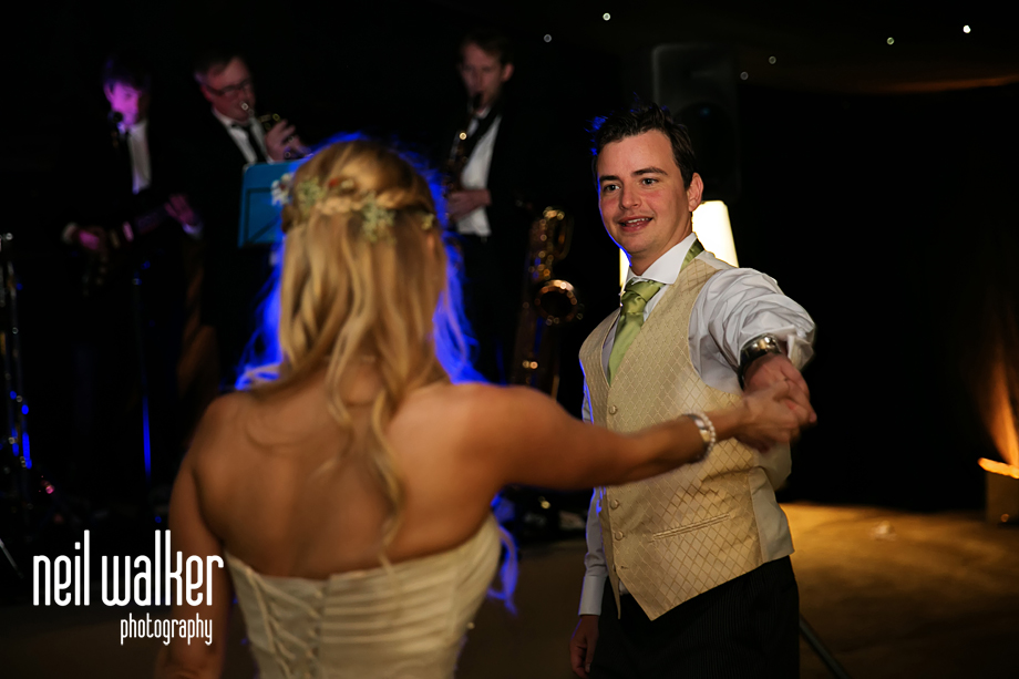 the groom looks at the bride as he dances with her