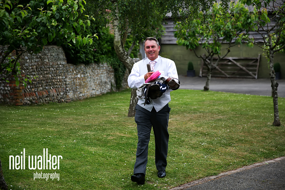 the bride's father walking across the lawn towards them