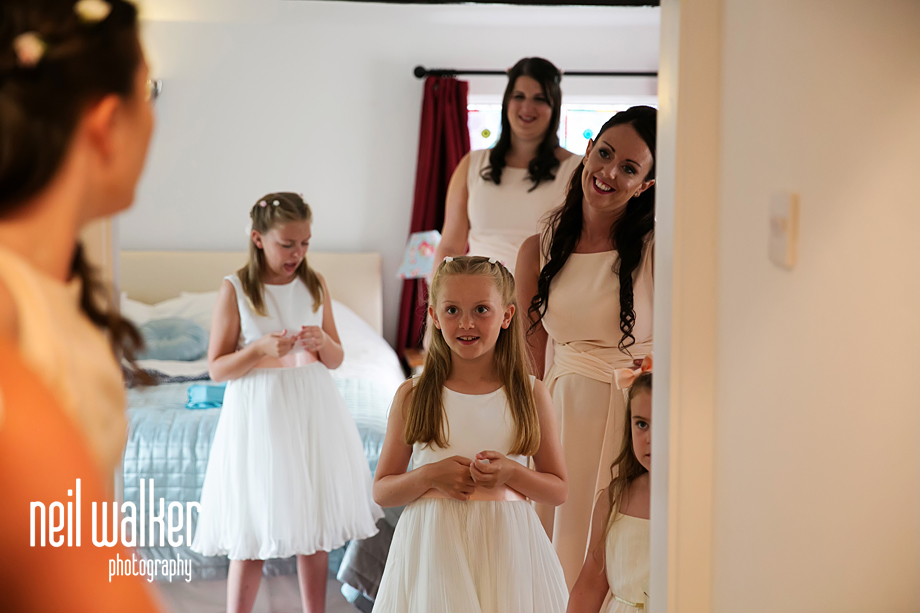 the bridesmaids watching as the bride's dress is being done up
