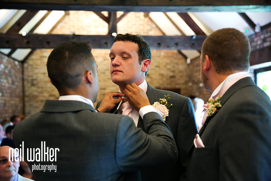 a groomsman adjusting the groom's cravat