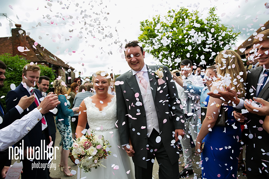 the bride & groom laugh as they walk through the confetti