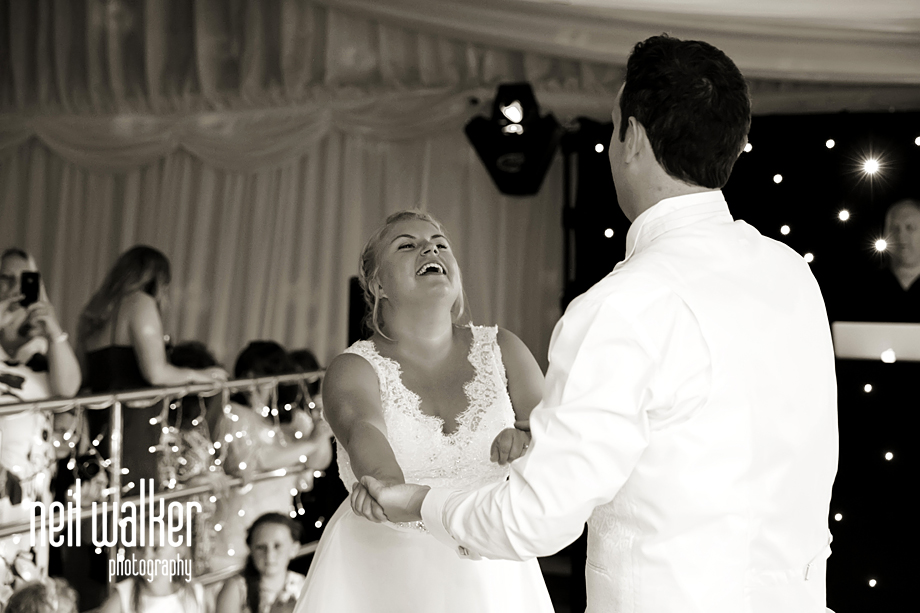 the bride & groom laughing as they do their first dance