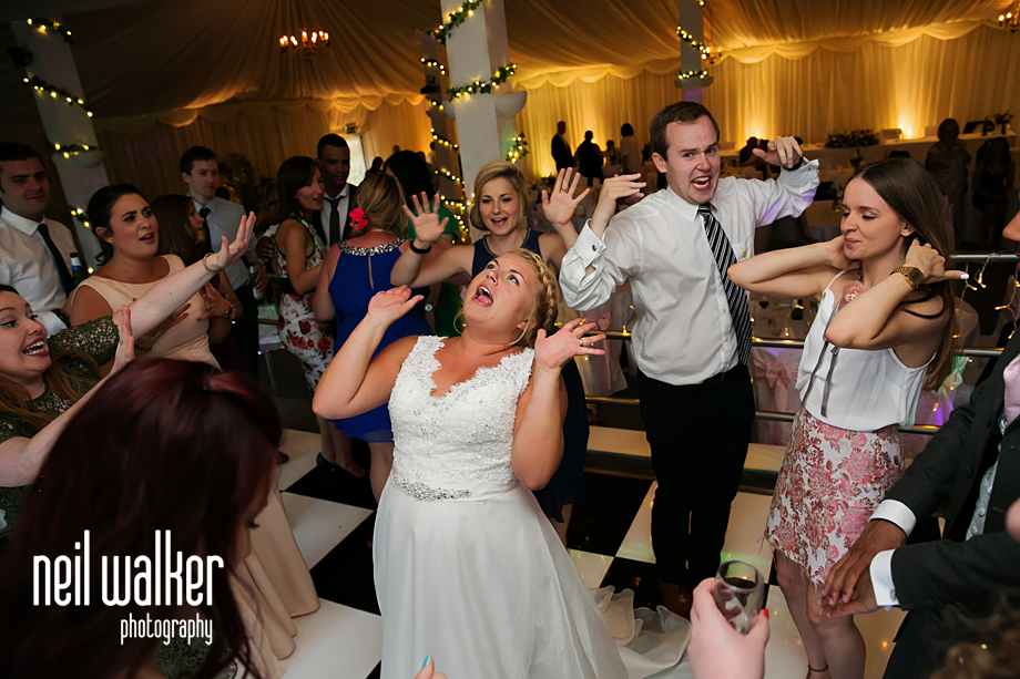 the bride in the middle as guests dance around them