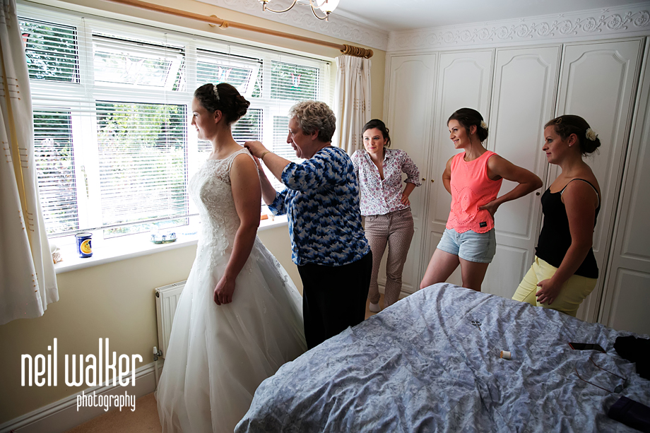 the bridesmaids helping the bride dress