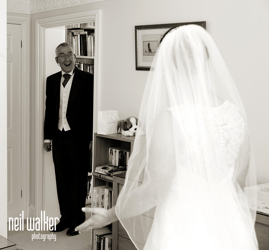 the father of the bride seeing her in her wedding dress for the first time