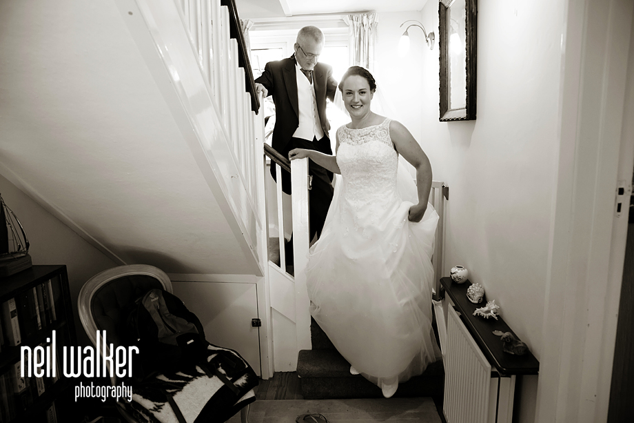 the bride lifting her dress to come down the stairs