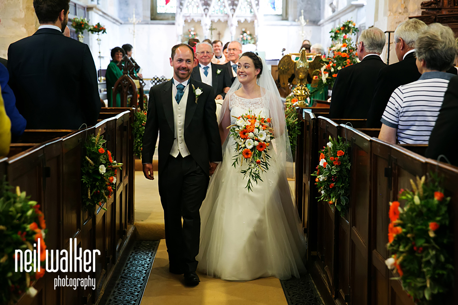 the wedding couple walking out of the church
