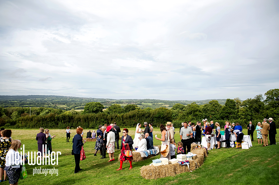 wedding guests talking in a field in East Sussex