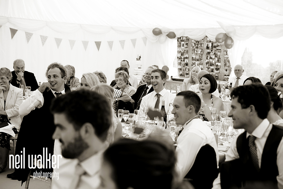 guests laughing at best man's speech
