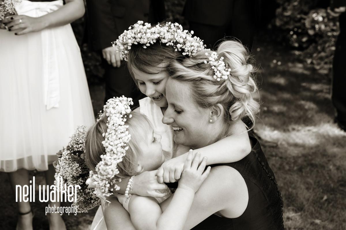 flower girls hugging a bridesmaid